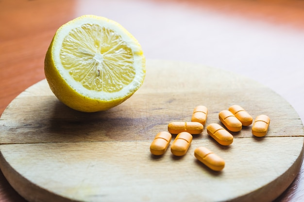 Pilules à côté d'un citron sur une surface en bois
