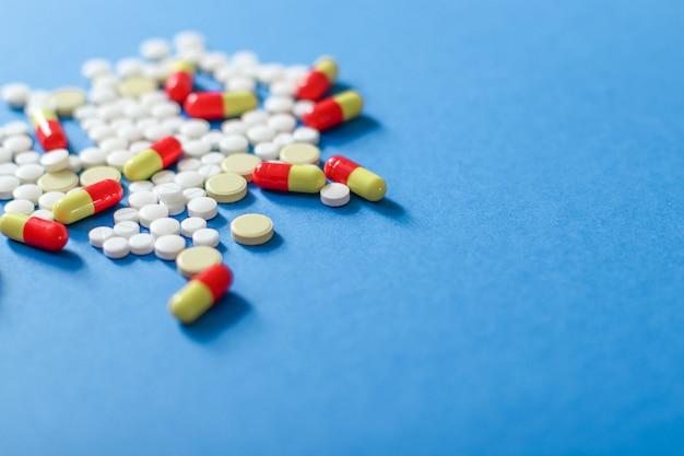 Pilules de couleur éparses isolés sur fond bleu.