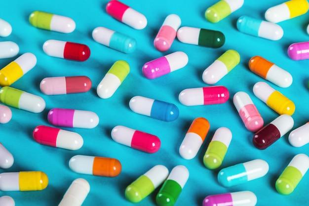 Pilules de couleurs différentes sur bleu