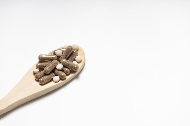 Pilules sur une cuillère en bois