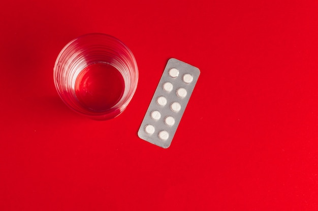 Pilules dans des ampoules avec un verre d'eau sur la vue de dessus rouge. médicament