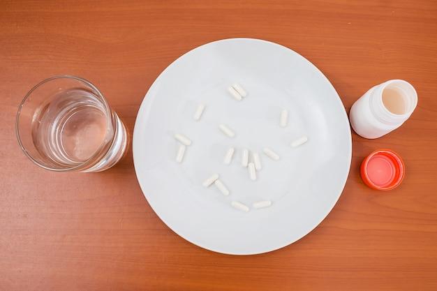 Pilules dans une assiette et un verre d'eau. vue d'en-haut.