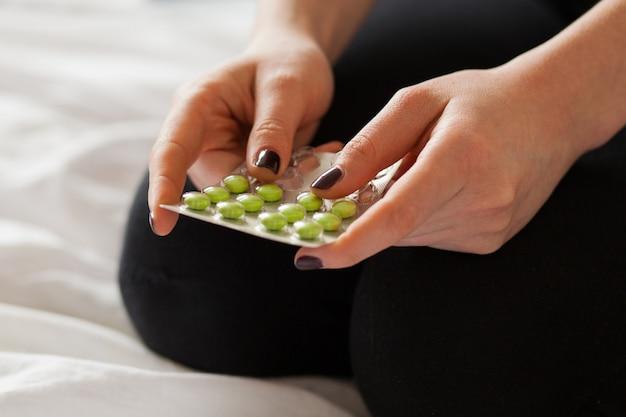 Pilules dans les mains d'une femme blanche