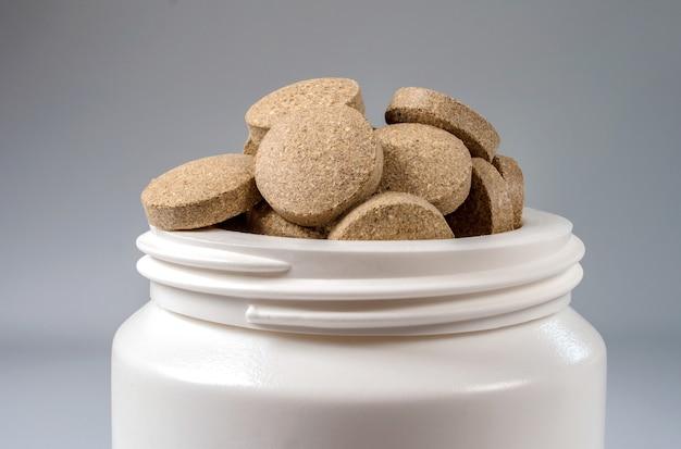 Pilules dans un pot en plastique blanc
