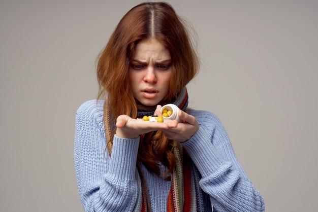 Pilules d'écharpe de cou de femme malade dans le fond d'isolement par main