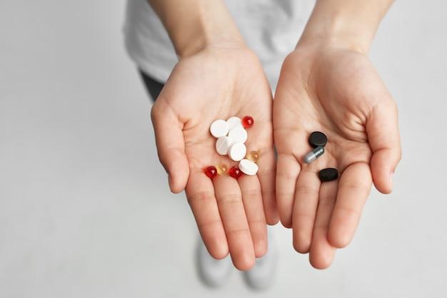 Pilules de femme malade dans le fond clair d'analgésique de main