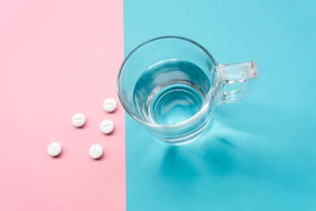 Pilules sur fond turquoise et rose pour la prévention, l'immunisation et le traitement de l'infection à coronavirus