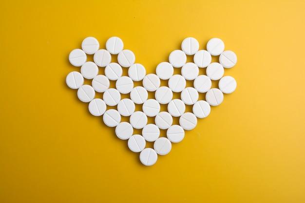 Pilules en forme de coeur sur fond jaune. lay plat, vue de dessus.