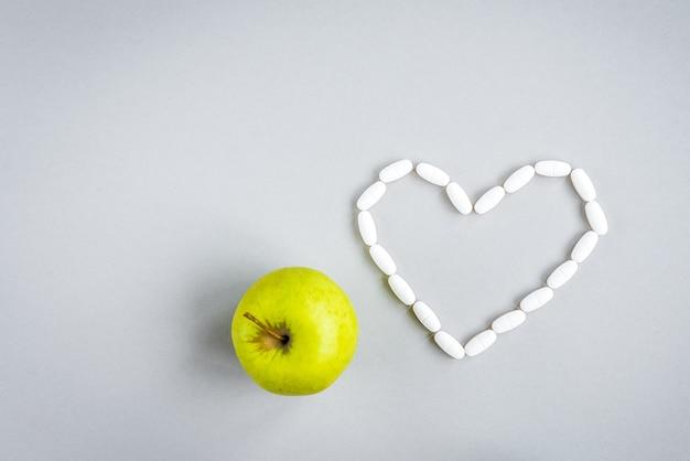 Pilules en forme de coeur avec pomme verte sur mur gris.