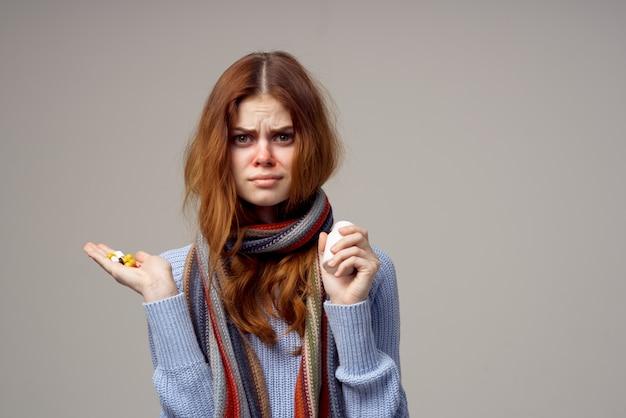 Pilules de foulard femme rousse dans la main fond isolé