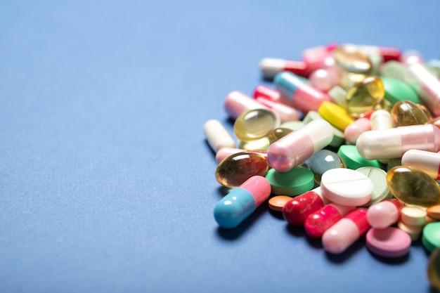 Pilules et gélules sur fond bleu, place pour le texte.