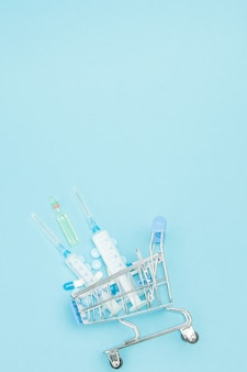 Pilules et injection médicale dans le caddie sur fond bleu. idée créative pour le coût des soins de santé, pharmacie, assurance maladie et concept d'entreprise de société pharmaceutique. copiez l'espace.