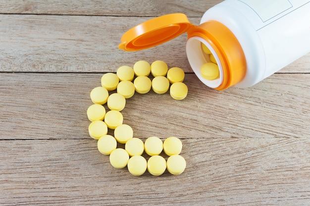 Pilules jaunes formant la forme à l'alphabet c sur fond de bois