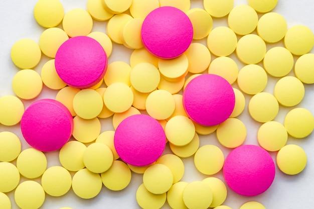 Pilules jaunes et roses sur blanc