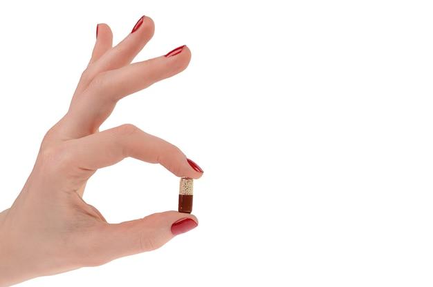 Pilules en main de femme isolé sur blanc