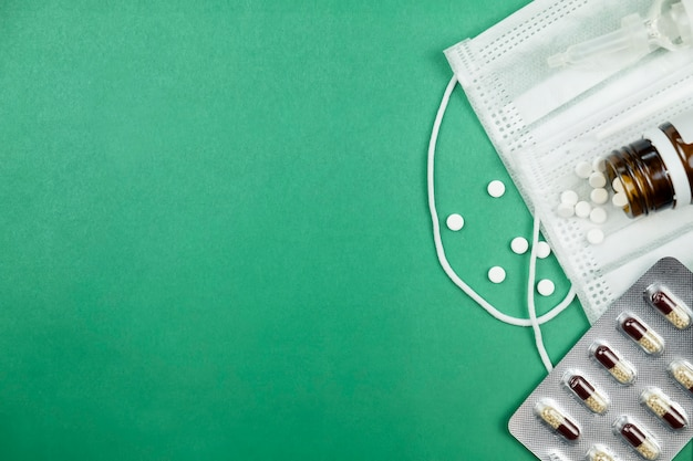 Pilules et masque de médecine sur fond vert avec espace de copie. vue de dessus