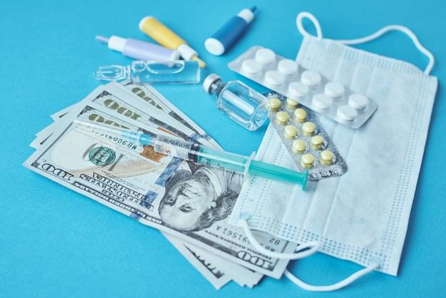 Pilules, masque de protection, articles médicaux et billets d'un dollar. concept de médecine coûteux. industrie pharmaceutique et assurance médicale