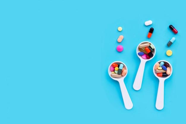 Pilules de médecine colorées, comprimés et capsules sur fond bleu