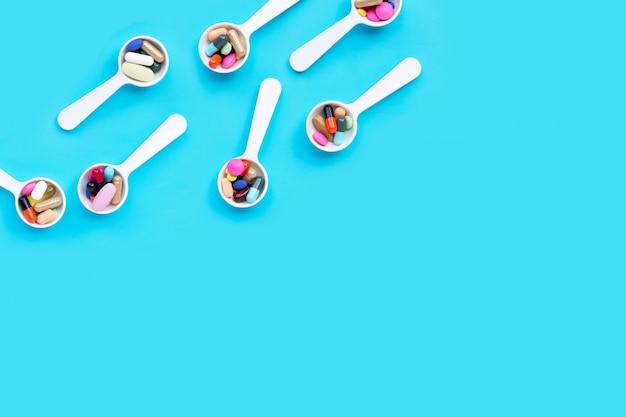 Pilules de médecine colorées, comprimés et capsules sur fond bleu.