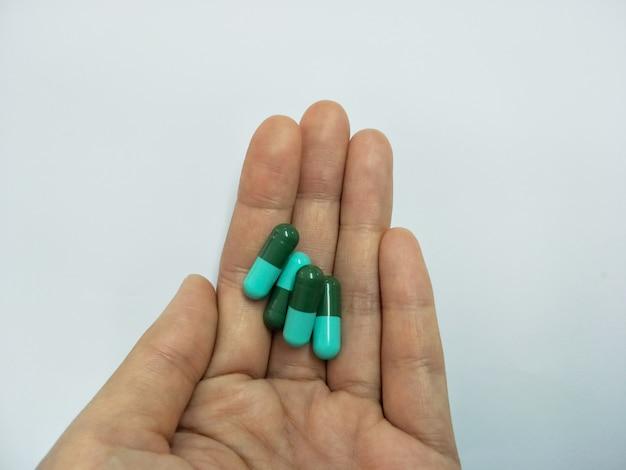 Pilules de médecine, comprimés et gélules à la main les femmes sur fond blanc