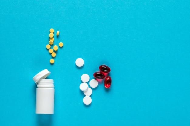 Pilules de médecine pharmaceutique, comprimés et bouteille sur bleu