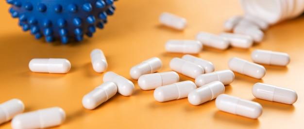 Pilules de médecine pharmaceutique, comprimés ou gélules et symbole de cellule covid-19 virus corona sur surface jaune.