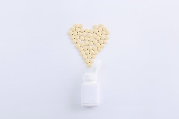 Pilules de médecine pharmaceutique débordant de bouteille de pilules en forme de coeur sur blanc