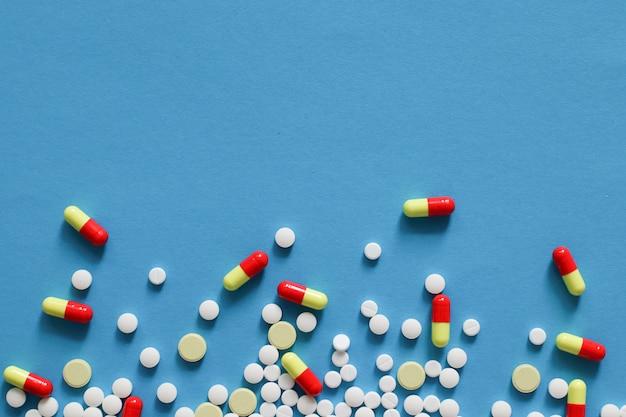 Pilules de médecine pharmaceutique éparses, comprimés et gélules isolés sur fond bleu.