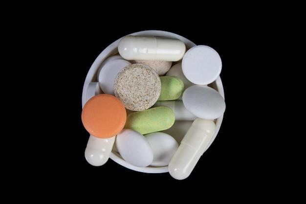 Pilules médicales et antibiotiques sur tableau noir. vue de dessus