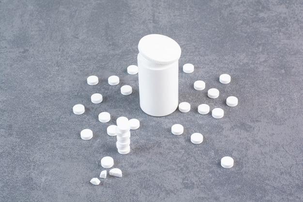 Pilules médicales blanches et récipient en plastique vide.