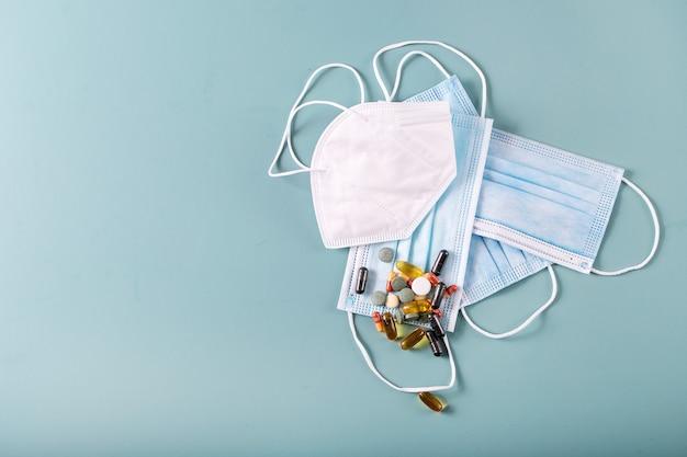 Pilules médicales et capsules avec masques médicaux sur fond de texture bleue. covid-19 [feminine. vue de dessus. copiez l'espace.