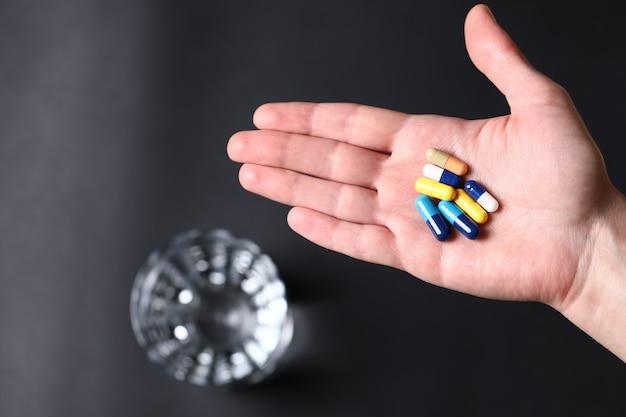 Pilules médicales colorées dans la main d'une personne et un verre d'eau