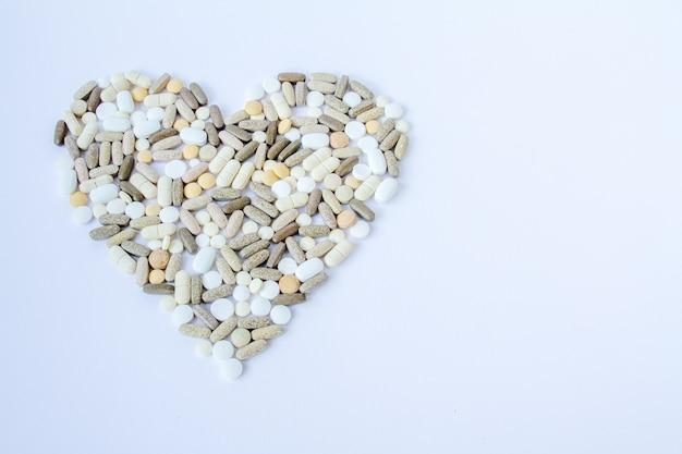 Pilules médicales colorées en vrac sur un fond blanc.