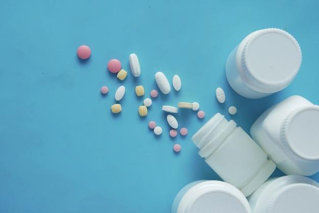 Pilules médicales de couleur blanche se déversant sur fond bleu