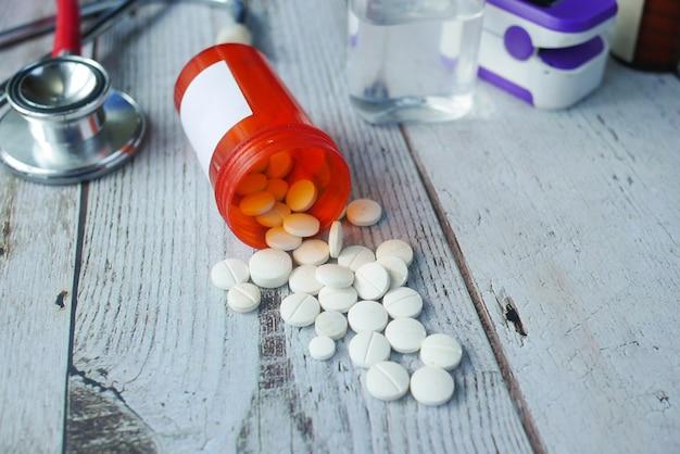 Pilules médicales de couleur blanche se déversant sur la table