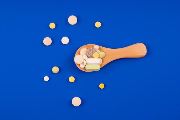 Pilules médicales avec une cuillère en bois sur fond bleu