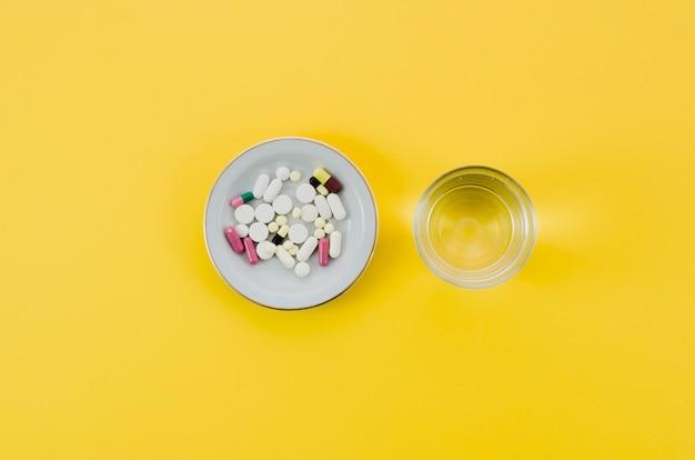 Pilules médicales dans un bol et un verre d'eau sur fond jaune