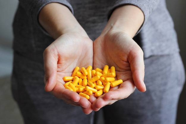 Les pilules médicales dans les mains des femmes prennent des pilules, des vitamines, des additifs alimentaires
