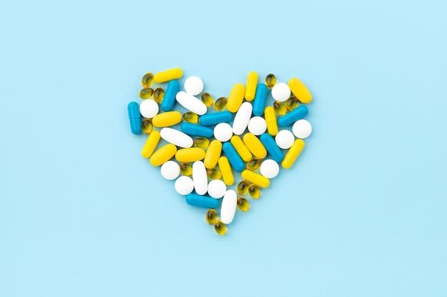 Pilules médicales en forme de coeur sur bleu
