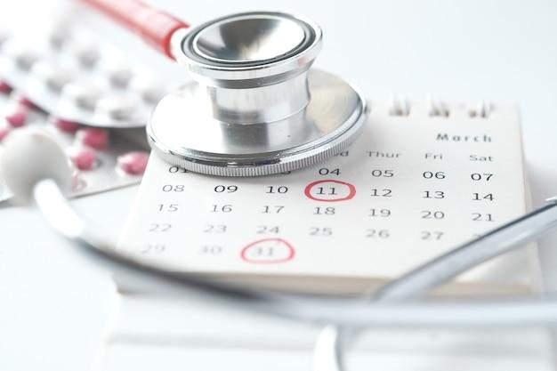 Pilules médicales et stéthoscope sur calendrier sur blanc