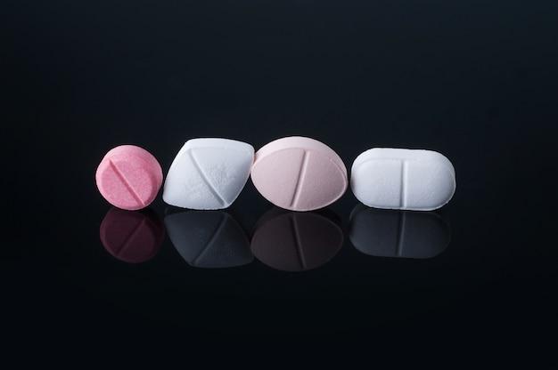Pilules médicales sur table en verre noir avec reflet.