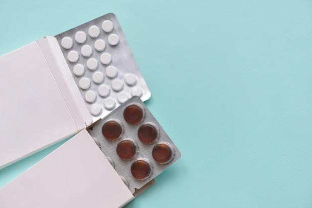 Pilules de médicaments dans des boîtes de papier sur un fond bleu isolé