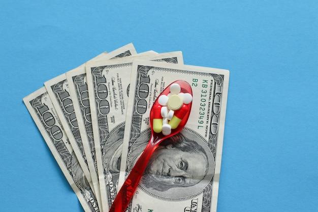 Pilules de médicaments pharmaceutiques éparses, comprimés et capsules sur une cuillère en plastique avec de l'argent. frais de médecine.