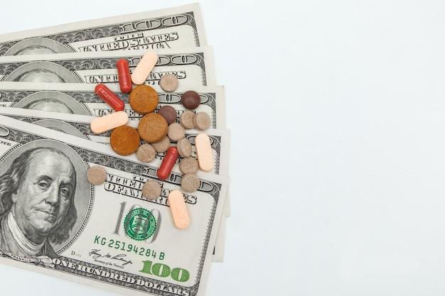 Pilules médicinales colorées et dollars américains sur blanc