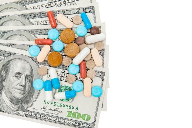 Pilules médicinales colorées et dollars américains sur un mur blanc