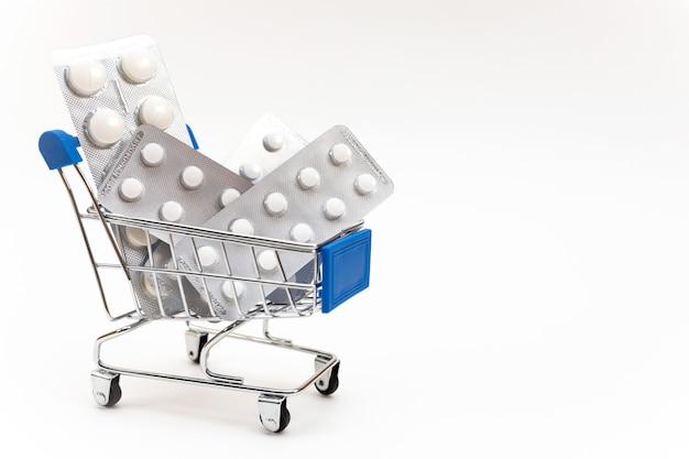 Pilules médicinales et vitamines dans un petit caddie dans un supermarché sur fond blanc