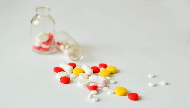 Pilules multicolores dans des bouteilles en verre transparent, sur un fond blanc. le concept de la médecine