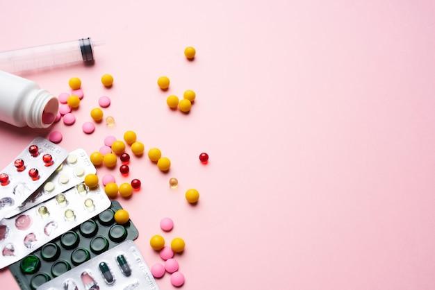 Pilules multicolores dans des emballages fournitures médicales soins de santé fond rose