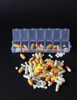 Pilules multicolores différentes avec boîte à pilules