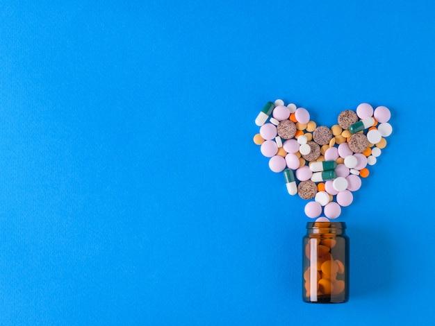 Des pilules multicolores en forme de coeur coulent d'une bulle de verre brune sur du bleu.